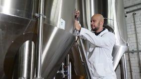 El empleado de los controles de la cervecería el equipo Máquina de funcionamiento del control del trabajador del mantenimiento en almacen de video