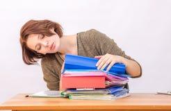 El empleado de oficina de la muchacha pasa cuidadosamente a través de una pila de carpetas Fotografía de archivo libre de regalías