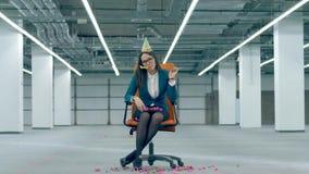 El empleado de oficina lanza confeti y sopla un silbido festivo, sentándose en una silla almacen de metraje de vídeo