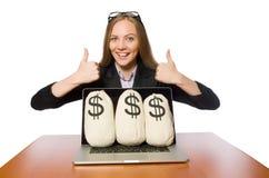 El empleado de sexo femenino con los sacos del dinero en su tabla fotos de archivo libres de regalías