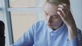 El empleado de sexo femenino está trabajando mientras que se sienta en la tabla en compañía grande metrajes