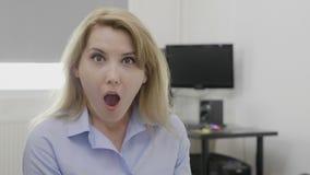 El empleado de sexo femenino joven hermoso que expresaba sorpresa y el mandíbula caído chocaron la reacción - metrajes