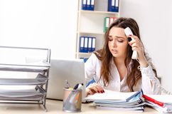 El empleado de sexo femenino joven infeliz con el trabajo excesivo foto de archivo