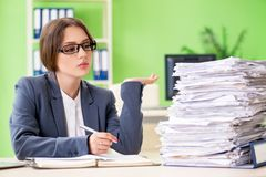 El empleado de sexo femenino joven muy ocupado con papeleo en curso fotos de archivo libres de regalías