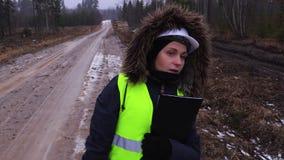 El empleado de sexo femenino de la silvicultura que camina e introduce el trabajo hecho almacen de metraje de vídeo