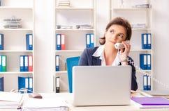 El empleado de sexo femenino de mediana edad que se sienta en la oficina fotos de archivo