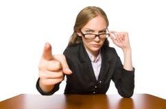 El empleado de sexo femenino que se sienta en la tabla larga aislada en blanco foto de archivo