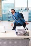 El empleado de sexo masculino encadenado infeliz con el trabajo excesivo foto de archivo