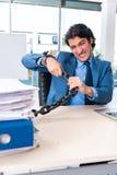 El empleado de sexo masculino encadenado infeliz con el trabajo excesivo fotografía de archivo libre de regalías