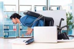 El empleado de sexo masculino encadenado infeliz con el trabajo excesivo imagen de archivo libre de regalías