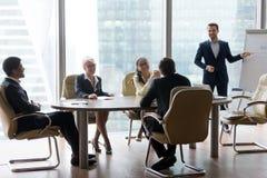 El empleado de sexo masculino hace la presentación en la reunión amistosa de la oficina fotografía de archivo