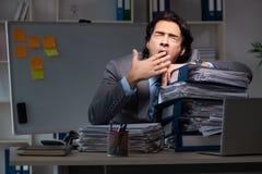 El empleado de sexo masculino joven que trabaja tarde en la oficina fotografía de archivo libre de regalías
