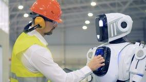 El empleado de sexo masculino de la fábrica está encendiendo a un cyborg y está regulando sus ajustes metrajes
