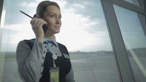El empleado del aeropuerto habla con el Walkietalkie en el fondo de la ventana metrajes