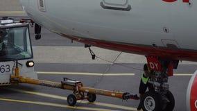 El empleado del aeropuerto saca la barra de remolque del aeroplano almacen de metraje de vídeo