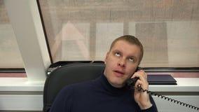 El empleado en la oficina escucha el interlocutor molesto por el teléfono metrajes