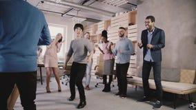 El empleado japonés feliz que hace movimientos divertidos de la danza en la celebración casual de la oficina va de fiesta El equi almacen de video