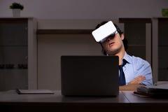 El empleado joven con los vidrios virtuales en la noche en la oficina fotos de archivo libres de regalías