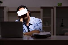 El empleado joven con los vidrios virtuales en la noche en la oficina imágenes de archivo libres de regalías