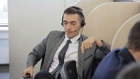 El empleado joven está hablando, usando las auriculares mientras que se sienta en oficina moderna almacen de metraje de vídeo