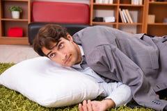 El empleado joven que duerme en el piso en la oficina imagenes de archivo