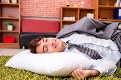 El empleado joven que duerme en el piso en la oficina fotos de archivo libres de regalías