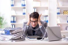 El empleado ocupado encadenado a su escritorio de oficina imagen de archivo