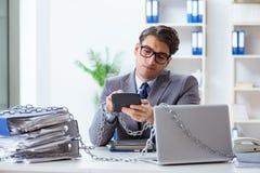 El empleado ocupado encadenado a su escritorio de oficina foto de archivo libre de regalías