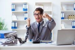 El empleado ocupado encadenado a su escritorio de oficina imagen de archivo libre de regalías