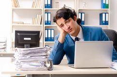 El empleado ocupado hermoso joven que se sienta en oficina fotos de archivo libres de regalías