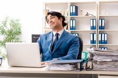 El empleado ocupado hermoso joven que se sienta en oficina foto de archivo