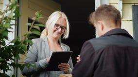 El empleado postal entrega el paquete Una mujer recibe una caja y firma su recibo almacen de metraje de vídeo