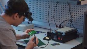 El empleado termina el trabajo sobre un nuevo módulo para la robótica Laboratorio de la robótica almacen de video