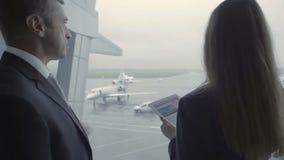 El empleado y el hombre de negocios del aeropuerto tienen una conversación en el aeropuerto cerca de ventana almacen de metraje de vídeo