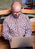 El empollón divertido habla en el ordenador portátil Fotos de archivo libres de regalías