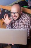 El empollón divertido habla en el ordenador portátil Foto de archivo