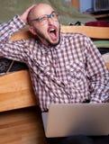 El empollón divertido habla en el ordenador portátil Imagen de archivo libre de regalías