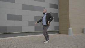 El empresario acertado talentoso en danza artística de la demostración del humor se mueve cerca de un edificio corporativo que si almacen de video