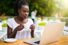 El empresario afroamericano joven encantador de la mujer se está sentando en el restaurante y tener de la calle sesión video en l fotos de archivo