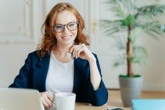 El empresario de sexo femenino acertado joven prepara el informe para el proyecto de inicio, busca la información sobre el ordena fotos de archivo