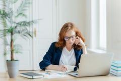 El empresario de sexo femenino confiado serio en ropa formal anota la información mientras que el negocio de los relojes webinar, fotos de archivo libres de regalías