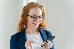 El empresario de sexo femenino positivo inteligente en la ropa elegante, feliz de recibir el mensaje en el teléfono móvil, descub foto de archivo