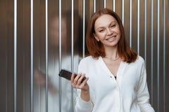 El empresario de sexo femenino satisfecho con sonrisa dentuda, lleva el puente blanco, sostiene el teléfono celular moderno, enví fotos de archivo