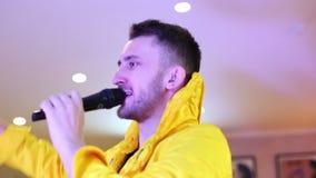 El empresario en traje de moda amarillo habla en un micrófono almacen de video