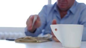 El empresario en un café y un hallazgo de la bebida de la pausa del trabajo añade en un periódico almacen de metraje de vídeo