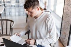 El empresario hermoso del hombre joven con un ordenador portátil en una camisa elegante está escribiendo en un cuaderno que se si fotografía de archivo libre de regalías