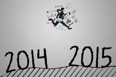 El empresario joven salta sobre el número 2014 a 2015 Foto de archivo