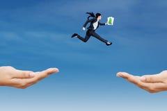El empresario salta a través de dos manos foto de archivo