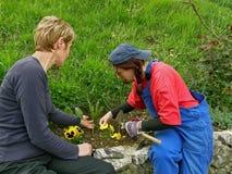 El empuje de dos mujeres y regula jardines de flor Fotos de archivo libres de regalías