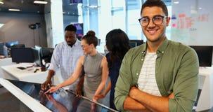 El enarenar ejecutivo masculino con los brazos cruzados mientras que colegas que trabajan en la oficina 4k metrajes